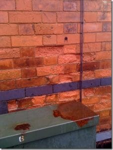 spalled and failing soft red bricks - dampness